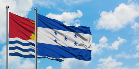Kiribati and Honduras flag waving in the wind against white cloudy blue sky together. Diplomacy concept, international relations.