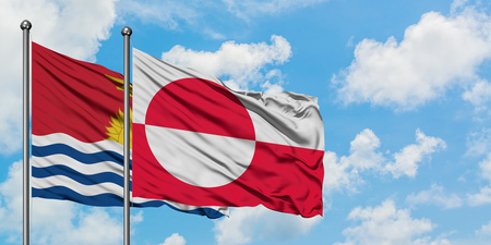 Kiribati and Greenland flag waving in the wind against white cloudy blue sky together. Diplomacy concept, international relations.