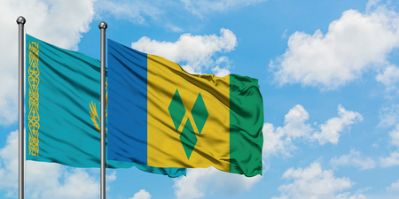 Kazakhstan and Saint Vincent And The Grenadines flag waving in the wind against white cloudy blue sky together. Diplomacy concept, international relations.