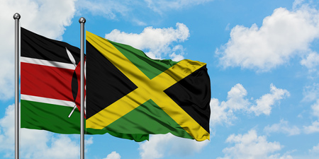 Kenya and Jamaica flag waving in the wind against white cloudy blue sky together. Diplomacy concept, international relations.