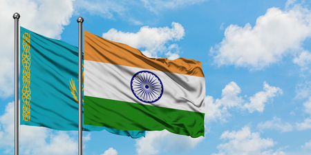 Kazakhstan and India flag waving in the wind against white cloudy blue sky together. Diplomacy concept, international relations. Stock Photo
