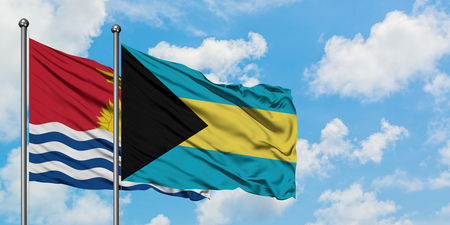 Kiribati and Bahamas flag waving in the wind against white cloudy blue sky together. Diplomacy concept, international relations. Stock Photo - 123793714