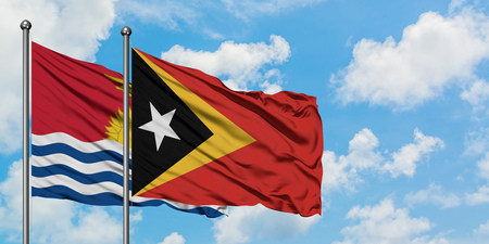 Kiribati and East Timor flag waving in the wind against white cloudy blue sky together. Diplomacy concept, international relations. 版權商用圖片