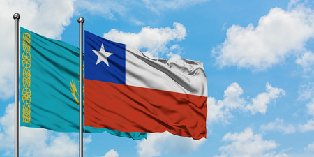 Kazakhstan and Chile flag waving in the wind against white cloudy blue sky together. Diplomacy concept, international relations.