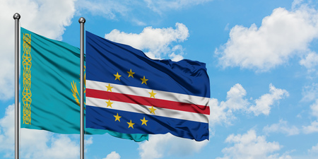 Kazakhstan and Cape Verde flag waving in the wind against white cloudy blue sky together. Diplomacy concept, international relations. 免版税图像