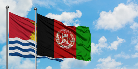 Kiribati and Afghanistan flag waving in the wind against white cloudy blue sky together. Diplomacy concept, international relations.