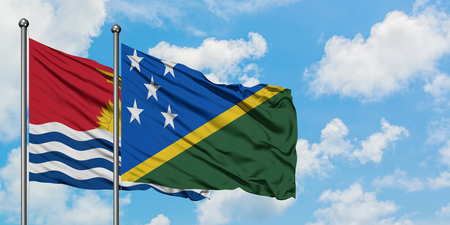 Kiribati and Solomon Islands flag waving in the wind against white cloudy blue sky together. Diplomacy concept, international relations.