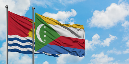 Kiribati and Comoros flag waving in the wind against white cloudy blue sky together. Diplomacy concept, international relations. 版權商用圖片