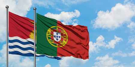 Kiribati and Portugal flag waving in the wind against white cloudy blue sky together. Diplomacy concept, international relations.