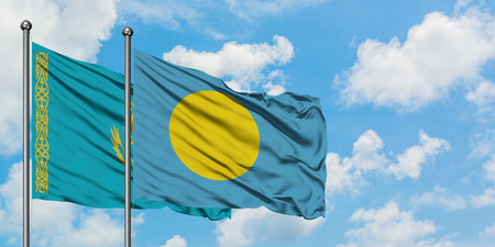 Kazakhstan and Palau flag waving in the wind against white cloudy blue sky together. Diplomacy concept, international relations.