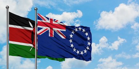 Kenya and Cook Islands flag waving in the wind against white cloudy blue sky together. Diplomacy concept, international relations. Stock Photo