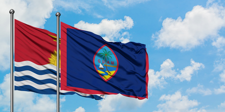 Kiribati and Guam flag waving in the wind against white cloudy blue sky together. Diplomacy concept, international relations. 版權商用圖片