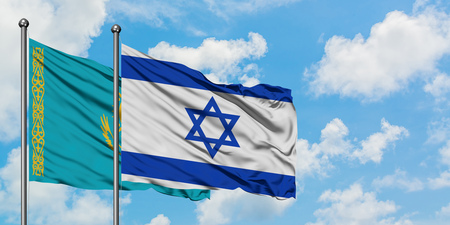 Kazakhstan and Israel flag waving in the wind against white cloudy blue sky together. Diplomacy concept, international relations.