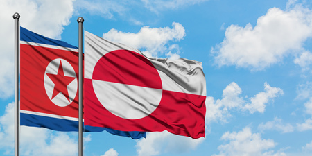 North Korea and Greenland flag waving in the wind against white cloudy blue sky together. Diplomacy concept, international relations.