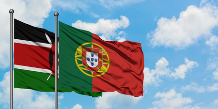 Kenya and Portugal flag waving in the wind against white cloudy blue sky together. Diplomacy concept, international relations. Stock Photo