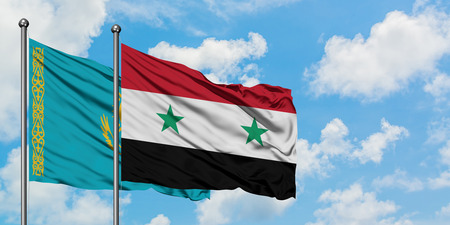 Kazakhstan and Syria flag waving in the wind against white cloudy blue sky together. Diplomacy concept, international relations. Stock Photo