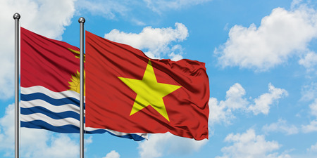 Kiribati and Vietnam flag waving in the wind against white cloudy blue sky together. Diplomacy concept, international relations. Stock Photo