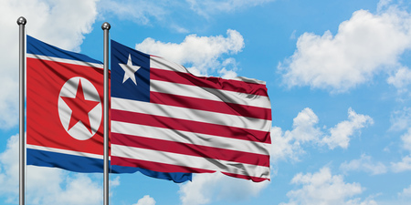 North Korea and Liberia flag waving in the wind against white cloudy blue sky together. Diplomacy concept, international relations.