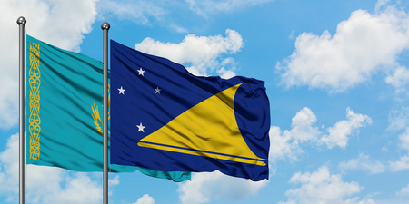 Kazakhstan and Tokelau flag waving in the wind against white cloudy blue sky together. Diplomacy concept, international relations. 免版税图像