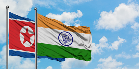 North Korea and India flag waving in the wind against white cloudy blue sky together. Diplomacy concept, international relations. Stock Photo