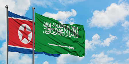North Korea and Saudi Arabia flag waving in the wind against white cloudy blue sky together. Diplomacy concept, international relations.