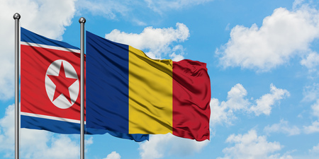 North Korea and Romania flag waving in the wind against white cloudy blue sky together. Diplomacy concept, international relations. Imagens