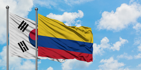 South Korea and Colombia flag waving in the wind against white cloudy blue sky together. Diplomacy concept, international relations.