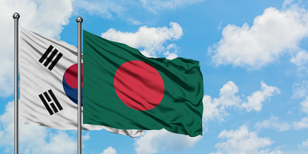 South Korea and Bangladesh flag waving in the wind against white cloudy blue sky together. Diplomacy concept, international relations.