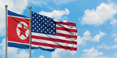 North Korea and United States flag waving in the wind against white cloudy blue sky together. Diplomacy concept, international relations.