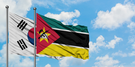 South Korea and Mozambique flag waving in the wind against white cloudy blue sky together. Diplomacy concept, international relations. Imagens