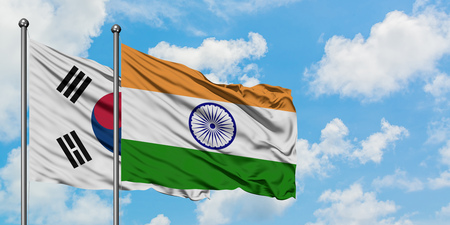 South Korea and India flag waving in the wind against white cloudy blue sky together. Diplomacy concept, international relations. Stock Photo