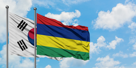 South Korea and Mauritius flag waving in the wind against white cloudy blue sky together. Diplomacy concept, international relations.
