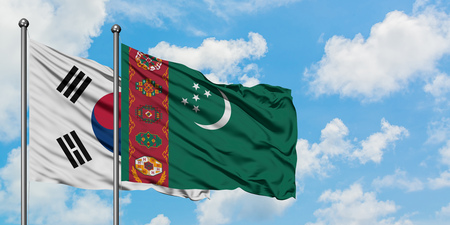South Korea and Turkmenistan flag waving in the wind against white cloudy blue sky together. Diplomacy concept, international relations.