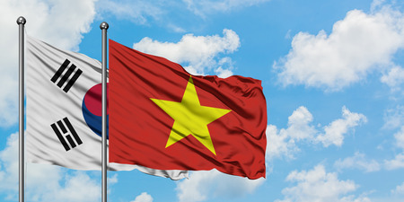 South Korea and Vietnam flag waving in the wind against white cloudy blue sky together. Diplomacy concept, international relations.