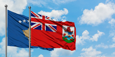 Kosovo and Bermuda flag waving in the wind against white cloudy blue sky together. Diplomacy concept, international relations. Imagens
