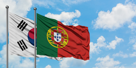 South Korea and Portugal flag waving in the wind against white cloudy blue sky together. Diplomacy concept, international relations. Imagens