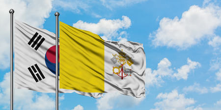 South Korea and Vatican City flag waving in the wind against white cloudy blue sky together. Diplomacy concept, international relations. 版權商用圖片