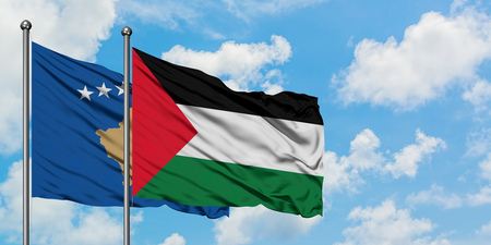 Kosovo and Palestine flag waving in the wind against white cloudy blue sky together. Diplomacy concept, international relations.