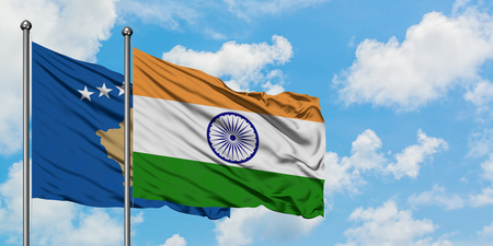 Kosovo and India flag waving in the wind against white cloudy blue sky together. Diplomacy concept, international relations.