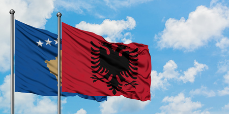 Kosovo and Albania flag waving in the wind against white cloudy blue sky together. Diplomacy concept, international relations. Archivio Fotografico