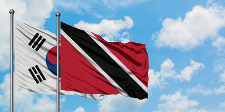 South Korea and Trinidad And Tobago flag waving in the wind against white cloudy blue sky together. Diplomacy concept, international relations. Imagens