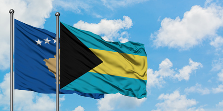Kosovo and Bahamas flag waving in the wind against white cloudy blue sky together. Diplomacy concept, international relations. Stock Photo - 123890001