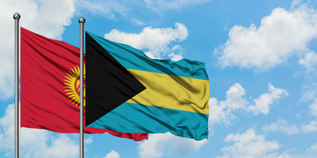 Kyrgyzstan and Bahamas flag waving in the wind against white cloudy blue sky together. Diplomacy concept, international relations. Stock Photo - 123888371