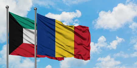 Kuwait and Romania flag waving in the wind against white cloudy blue sky together. Diplomacy concept, international relations.