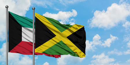 Kuwait and Jamaica flag waving in the wind against white cloudy blue sky together. Diplomacy concept, international relations. Stockfoto