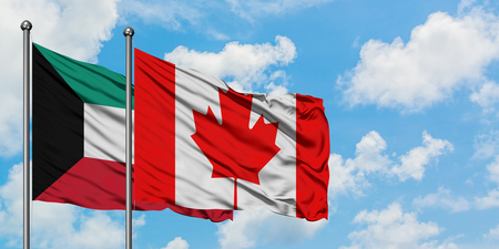 Kuwait and Canada flag waving in the wind against white cloudy blue sky together. Diplomacy concept, international relations. Stock Photo