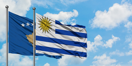 Kosovo and Uruguay flag waving in the wind against white cloudy blue sky together. Diplomacy concept, international relations.