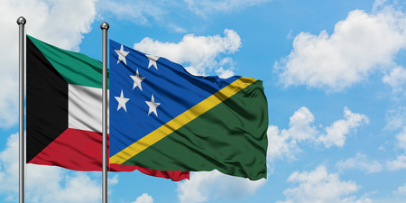 Kuwait and Solomon Islands flag waving in the wind against white cloudy blue sky together. Diplomacy concept, international relations. Stok Fotoğraf