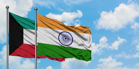 Kuwait and India flag waving in the wind against white cloudy blue sky together. Diplomacy concept, international relations.