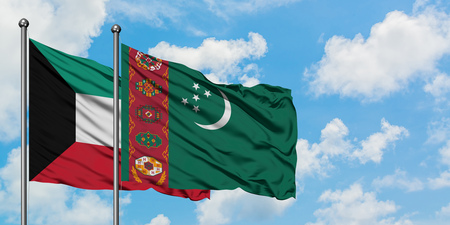 Kuwait and Turkmenistan flag waving in the wind against white cloudy blue sky together. Diplomacy concept, international relations. Stock Photo